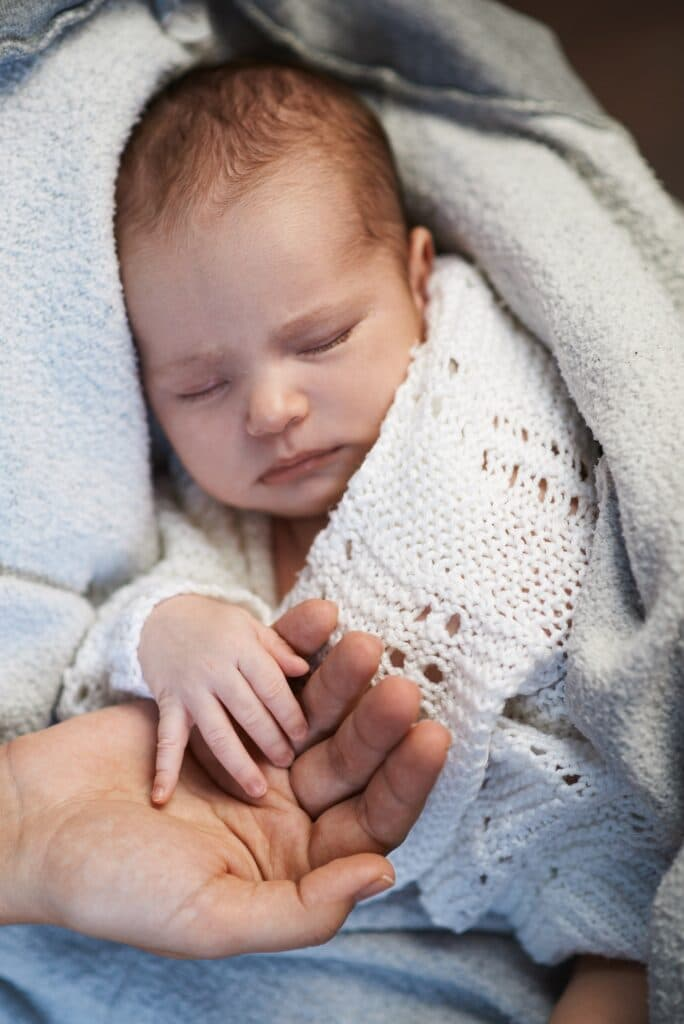 Mom keeps miniature hand newborn baby in hands